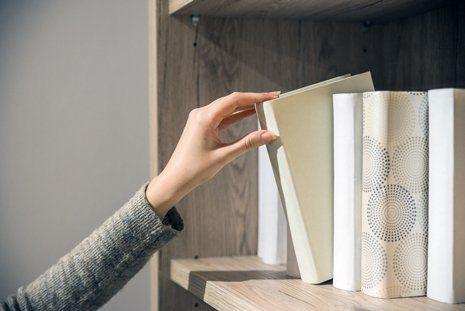 mano femminile prende un libro da una mensola
