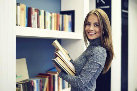 giovane ragazza posa  libri su una libreria