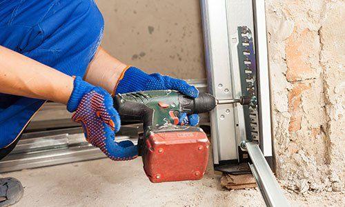 un uomo con guanti blu e arancioni e un trapano sta installando la porta di un box a Trieste