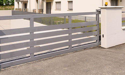 vista di un cancello automatico color grigio all'entrata di un condominio