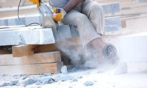 avoratore industriale rendendo taglio orizzontale con la mano sega elettrica durante piastrelle di marmo align