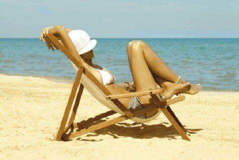 una donna al mare sdraiata sul lettino
