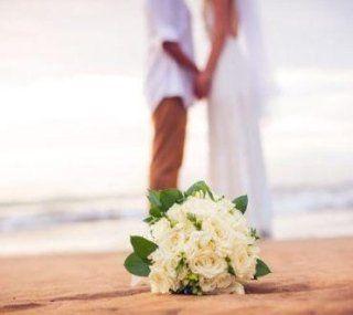 una coppia sulla spiaggia con mazzo di fiori