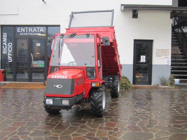 un trattore rosso con il rimorchio ribaltabile