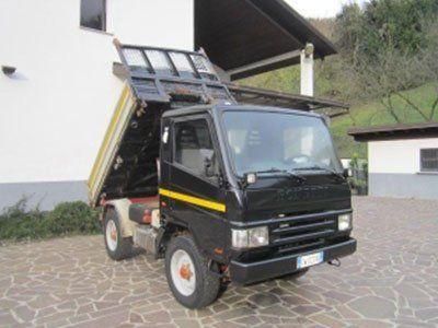 un camion nero con rimorchio ribaltabile