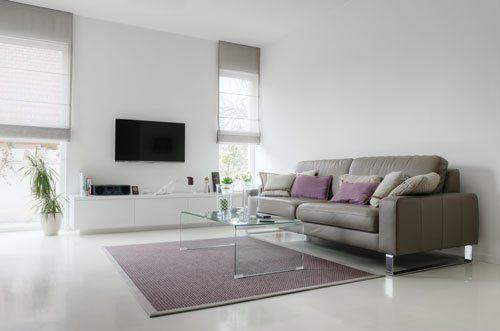un salotto moderno con sulla destra un divano in pelle color marrone, un tavolino e vista di una tv a muro