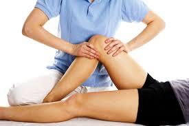 un tecnico comprime il ginocchio della gamba piegata di un paziente