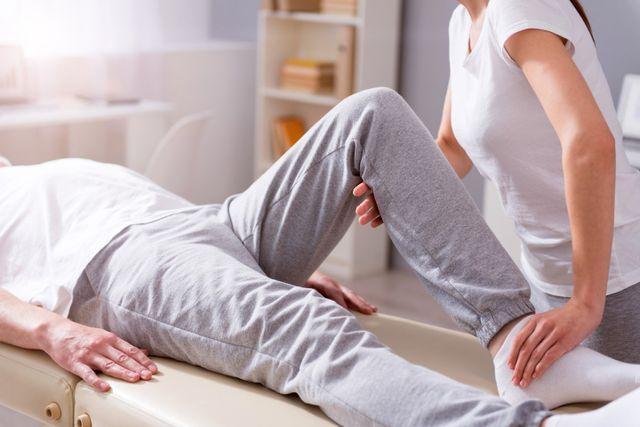 un tecnico piega la gamba di un paziente sdraiato