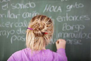 Female student during Spanish Class in front of a blackboard