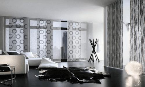 una sala con un divano bianco un tappeto nero e delle tende bianche e grigie