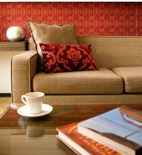 un tavolino con sopra dei libri,una tazza e di fronte un divano beige con dei cuscini