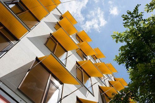 delle tende arancioni su delle finestre di un palazzo