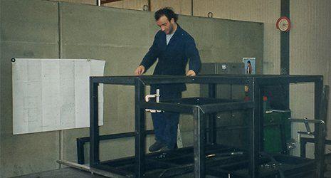 un operaio con tenuta blu vicino a un telaio assemblato a Piacenza