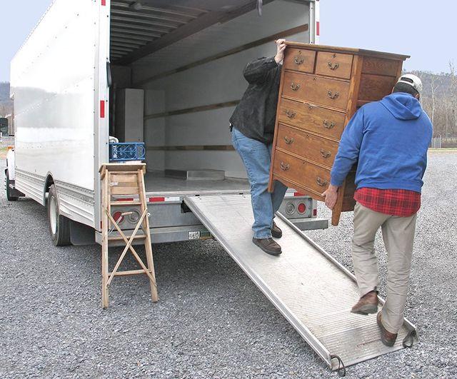 dei traslocatori che scaricano dal camion una cassettiera di legno