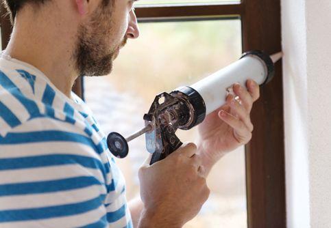 Man applying silicone sealant in a window