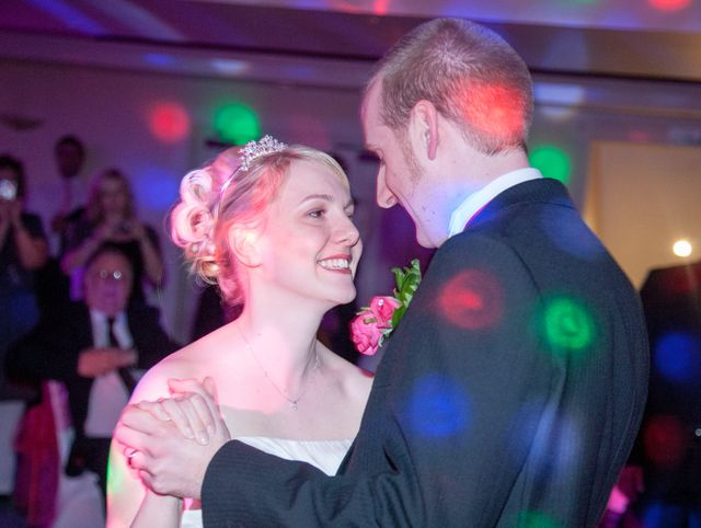 Green and red lights on a bride and groom dancing together