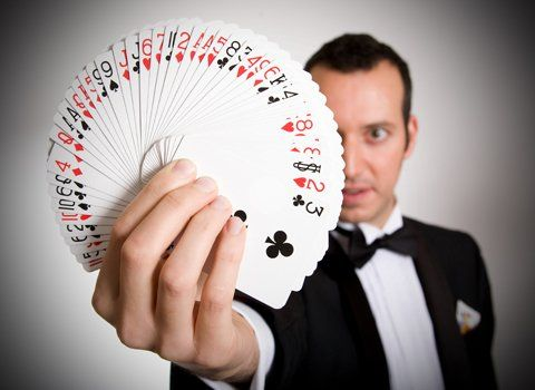 A magician in a tuxedo, holding fanned-out playing cards in one hand