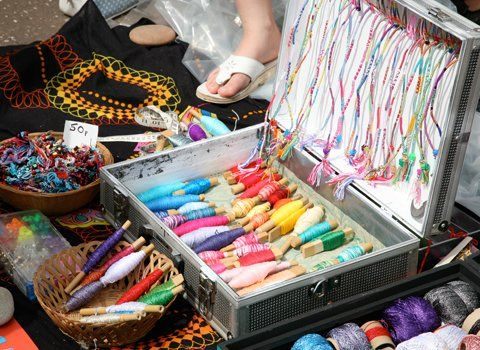 A table full of hand made bracelets in different colours and styles
