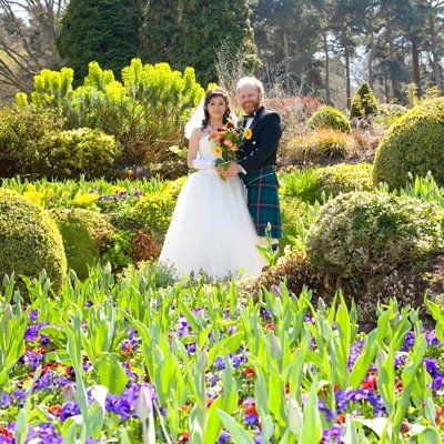 A bride in white, and a groom in a kilt, in the middle of a garden of flowers and shrubs