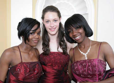 Three girls wearing prom dresses in shades of burgundy