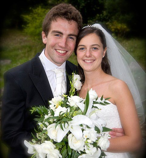 A smiling groom in white tie and black suit, with his bride in white, holding a bouquet of white flowers