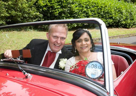 A bride and groom in an open top red sports car