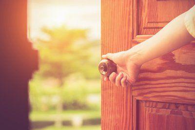 mano che apre una porta in legno