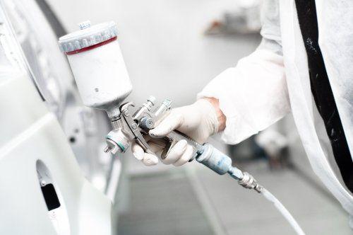 Operaio protetto dipingendo un auto di bianco