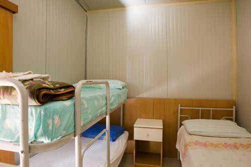 una stanza con sulla sinistra un letto a castello, in centro un comodino e sulla destra un letto singolo