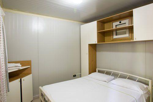 piccola stanza con sulla sinistra un armadietto bianco e marrone, sulla destra un letto e sopra un mobile a ponte bianco e marrone
