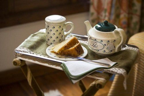 Vassoio da portata con una teiera, una tazza e un piatto con due porzioni di pan di spagna