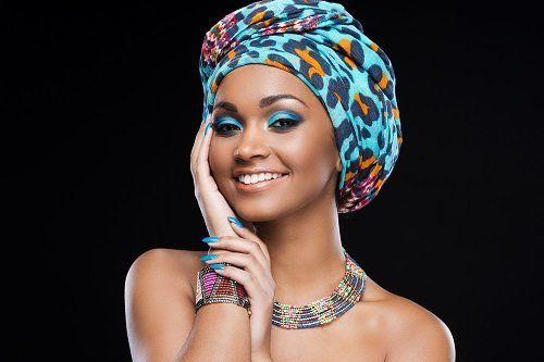 una donna con un foulard in testa di diversi colori, una collana e un bracciale