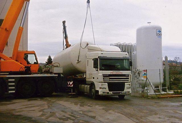 un asfaltatrice,degli operai e dei camion con rimorchi container ribaltabili