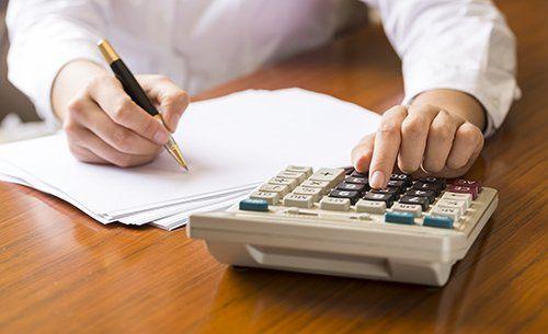Un uomo preme dei tasti su una calcolatrice