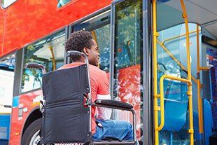 young man in wheelchair in front of a buss