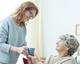 a woman offering tea to another elderly woman