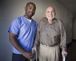 young man nurse helping elderly man