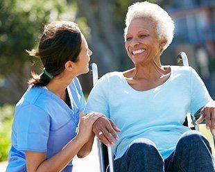 senior woman in wheel chair helped by a nurse