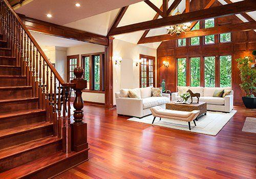 Accogliente stanza, grandi finestre,pavimento in legno, scale di legno , sofà di colore chiaro, travi decorando il tetto