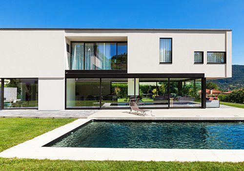 Casa di stile geometrico, grandi finestre,,piscina e giardino