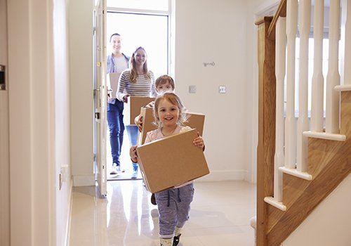 Famiglia sorridente che entra nella casa
