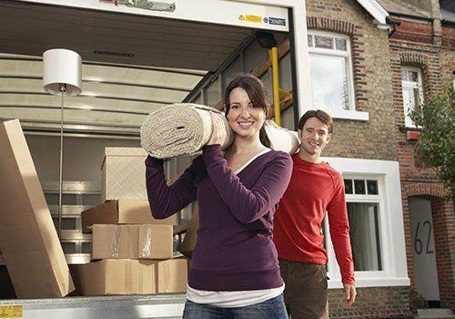 Un camion di traslochi e una coppia giovane con un tappeto