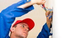 operaio mentre taglia dei fili elettrici con forbici da elettricista