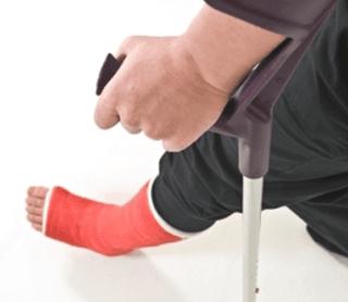 Primo piano di un ragazzo con piede ingessato e stampelle