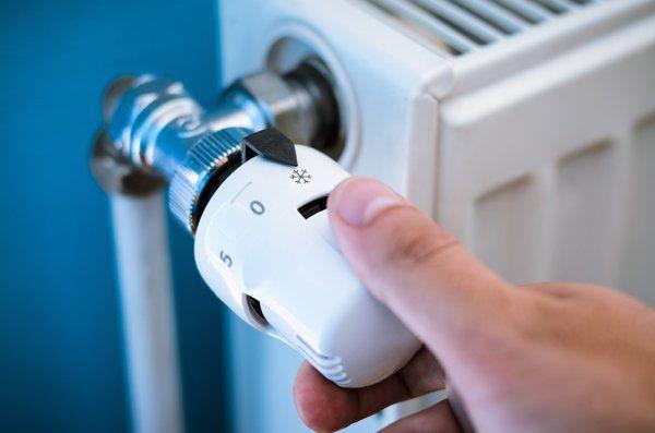 una mano ruota la manopola di un termosifone