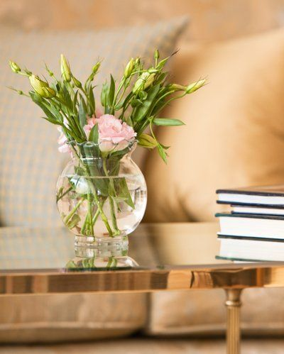 Coffee table with vase of pink flowers on top