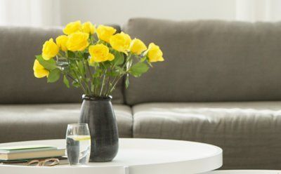 Coffee table with vase of yellow flowers on top