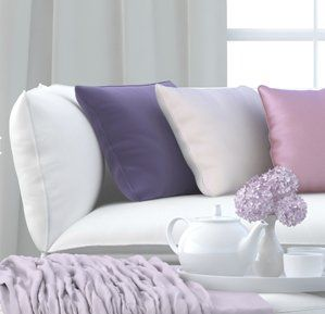 White sofa with purple cushions on
