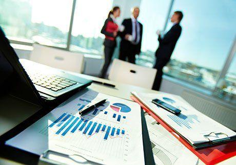 mago di documenti aziendali sul posto di lavoro con tre partner che interagiscono su sfondo