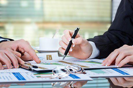 Gli uomini d'affari che lavorano con grafici di analisi foglio